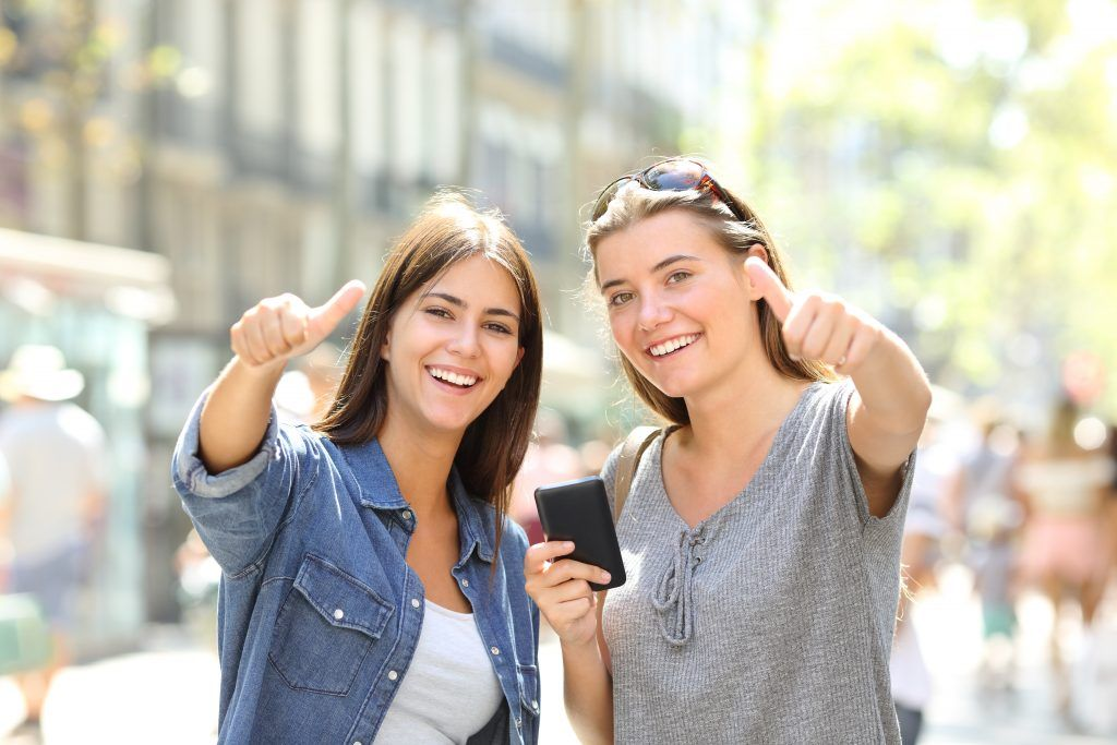 Friends Holding Phone Looking At You With Thumbs Up