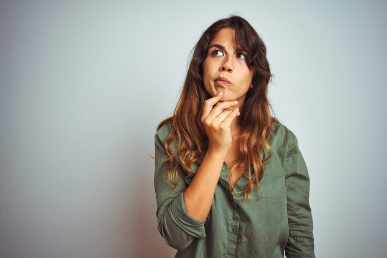 Young Beautiful Woman Wearing Green Shirt Standing Over Grey Isolated Background Thinking Concentrated About Doubt With Finger On Chin And Looking Up Wondering